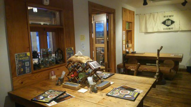 木製のドアや壁のタペストリーとテーブルの上のワインの空き瓶やメニュー表