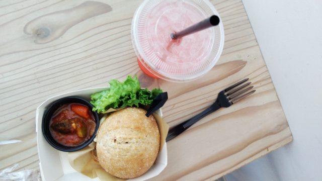 テーブルの上のスペシャルバーガーとピンクグレープフルーツジュースとフォーク