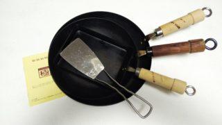 重ねて置いた鉄のフライパン3種類とフライ返し