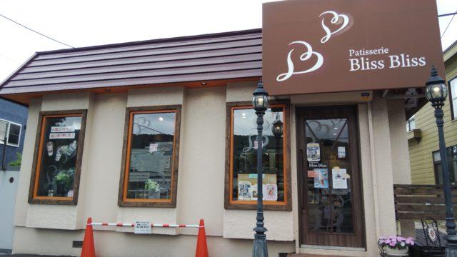 茶色い看板と茶色い屋根のお店外観
