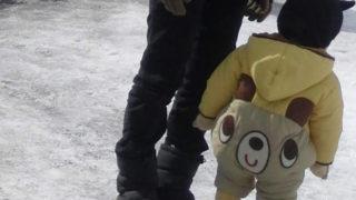 クマのスノーウェアを着た子供の後ろ姿