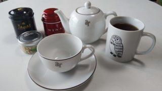 ティーポットとティーカップとお茶の入ったマグカップと紅茶の缶3つ