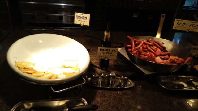 目玉焼きが入ったフライパンとベーコンとウインナーが入ったフランパン