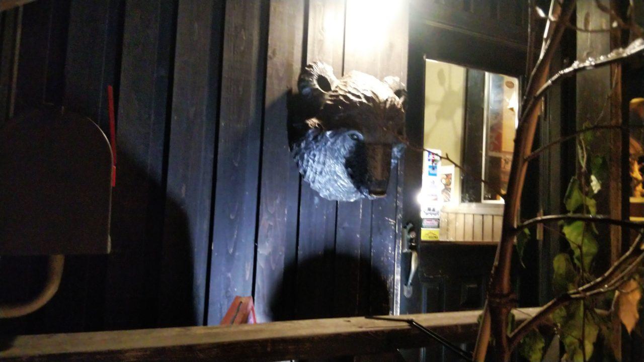 入口ドアとヒグマの顔の飾りと木の枝